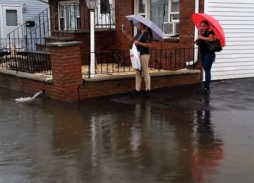 Women are stuck in the flooding in front of Rocco Falzone's house during a recent rainstorm. (Courtesy photo, Rocco Falzone)