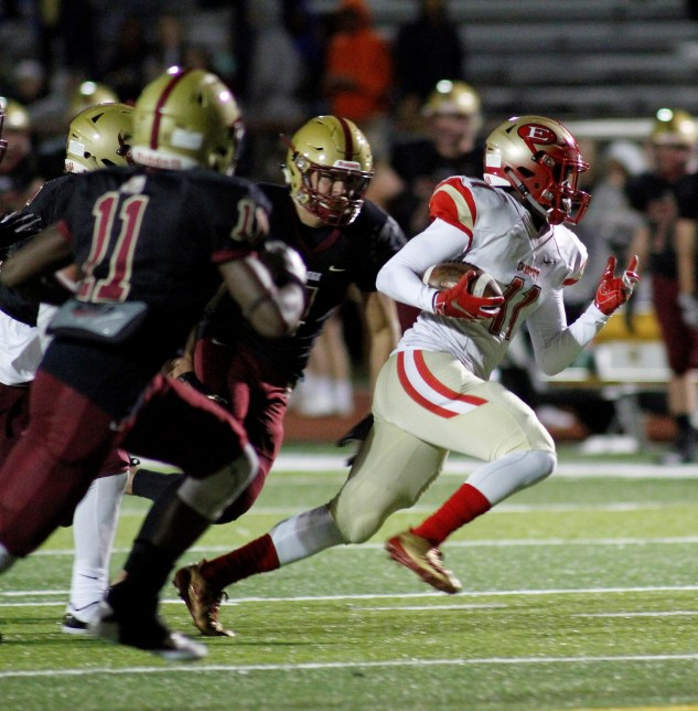 Sophomore running back Tyrese Baptiste pulls away from a host of BC High defenders.