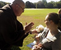 Rev. Michael Otero-Otero of the St. Clare of Assisi Catholic Community blesses Gracie, an 11-week-old Maltese Poodle, owned by Stephanie Ataide of Peabody.