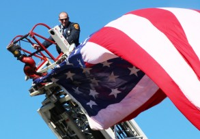 Malden Fire Fighter Michael Angelo prepares the flag for the ceremony.