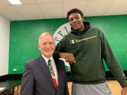 """Superintendent of School Frederick Foresteire visibly notices the height difference between himself and Celtics player Rob Williams, who is 6'10""""."""