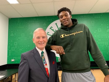 "Superintendent of School Frederick Foresteire visibly notices the height difference between himself and Celtics player Rob Williams, who is 6'10""."