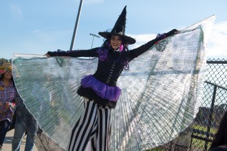 Gina DeFreitas, a stilt walker from Big Smile Entertainment, waved her cape in the wind.