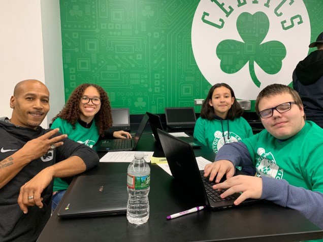 Celtics legend Dana Barros gives a peace sign as he interacts with students Laura Castilho, Salma Abderazzak and Jordan Vautour on a science project.
