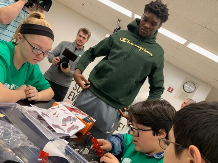 Boston Celtics rookie Rob Williams watches students Makenzie Powers, Kevin Da Fonseca and Brian Alanis as they work on a robotics project.