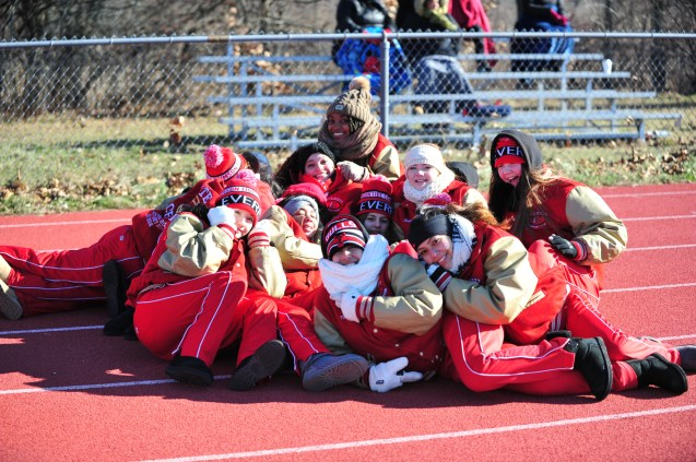 WARMING-UP: Members of the talented Crimson Tide cheerleaders found a way to keep warm a the T-Day game by huddling together in frigid temperature before the Tide blanked Masco, 32-0 to end a fabulous 10 wins – 1 loss season.