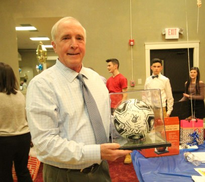 Peabody head coach Stan McKeen with a ball signed by players from all three teams. McKeen was named this year's Coach of the Year in the Northeastern Conference North.