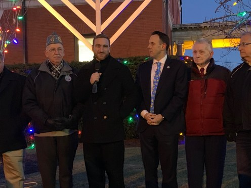 Temple B'Nai Israel Rabbi Reb Misha Clebaner, who identifies himself as Reformed Jewish, in center, made a joke about the freezing temperatures (approximately 30 degrees) and how it warmed his heart to see so many people come out and celebrate together in full show of support for the city's Jewish residents during Tuesday's Menorah Lighting Ceremony.
