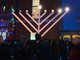 Mayor Brian Arrigo lights the second menorah candle on Tuesday afternoon in front of City Hall.