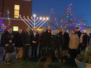 Community members gather in front of the lit menorah.
