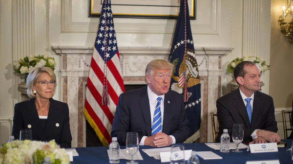President Donald Trump, flanked by Education Secretary Betsy DeVos, left, and Labor Secretary Alexander Acosta, answers questions in August of 2017, at Trump National Golf Club in Bedminster, N.J. Today the White House announced plans to merge the two departments.