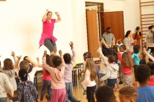 Instrutora de dança com alunos a dançar