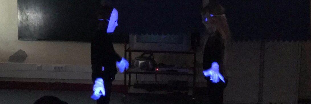 Dois alunos com máscaras e luvas brancas a brilhar na penumbra