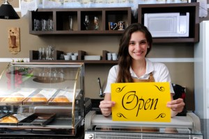 Multi-location business owner holding Open sign