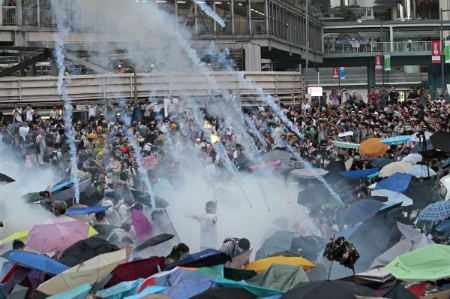 Protesters with umbrellas open as tear gas cannisters fly at them.