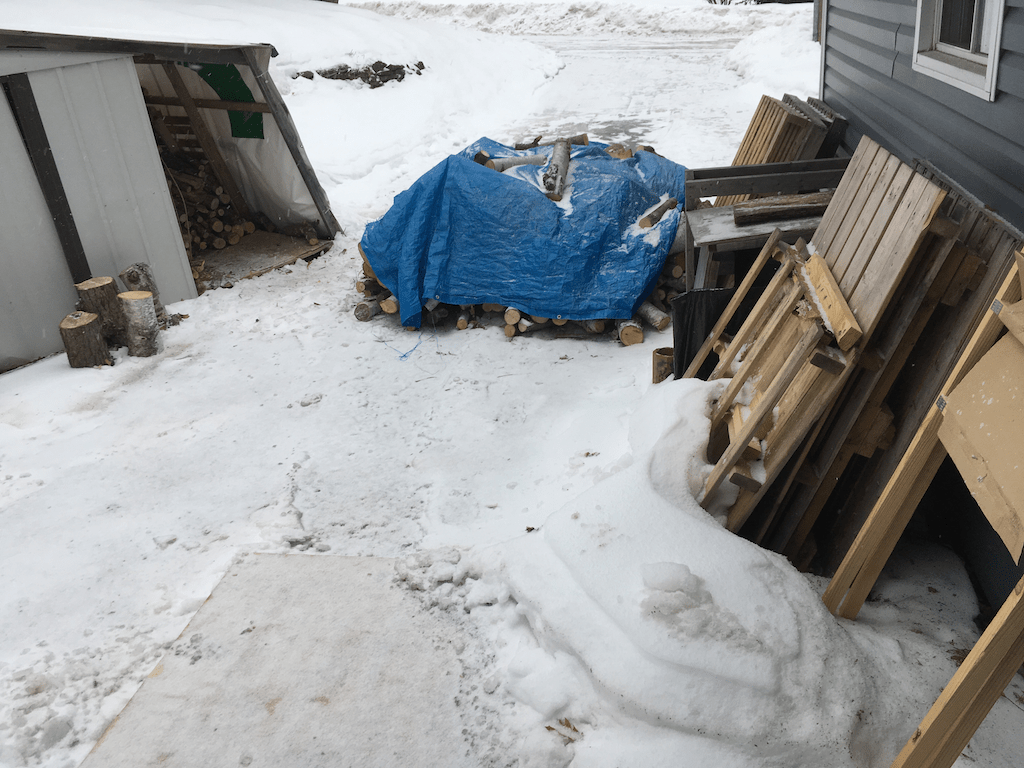 Wood pile under tarp in drveway with very slight accumulation of snow flurries.