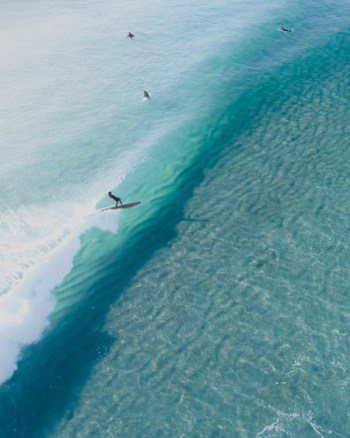 Aerial Of Longboarder Riding Wave