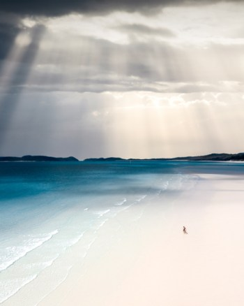 A Couple Walks The White Sands Of The Whitsundays As The Sun Rays Comes Through The Clouds