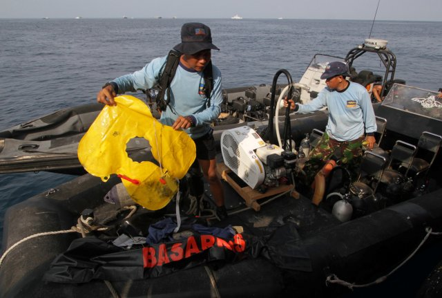 Indonesian Navy member holds a lifejacket recovered after the airplane's sea crash, off the coast of Karawang regency