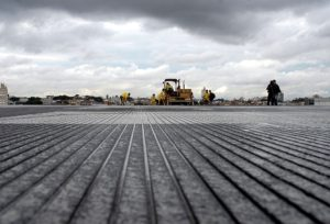 Low angle photo of a runway surface. Grooves can be seen. They are about the width of a quarter and spaced about an inch apart.