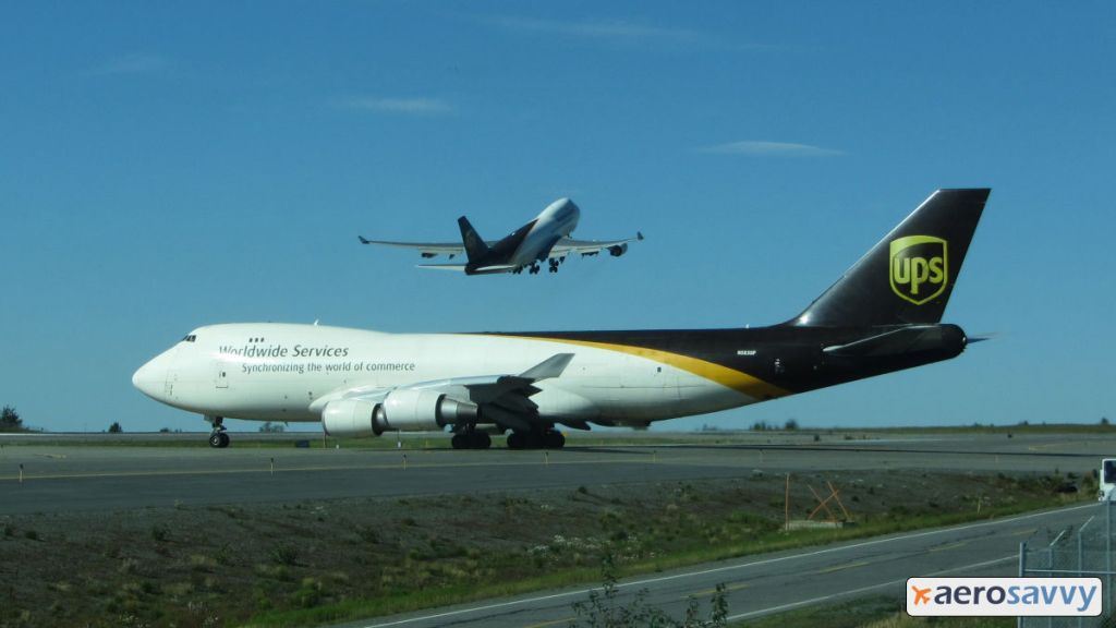 A UPS 747 on a taxiway as another UPS 747 lifts off behind it. You might be a cargo pilot... - AeroSavvy