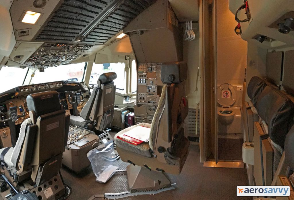 767 Freighter cockpit. Two pilot seats with observer seat behind and between the seats. Just behind observer seat is the lavatory with door open. Toilet can be seen. - AeroSavvy