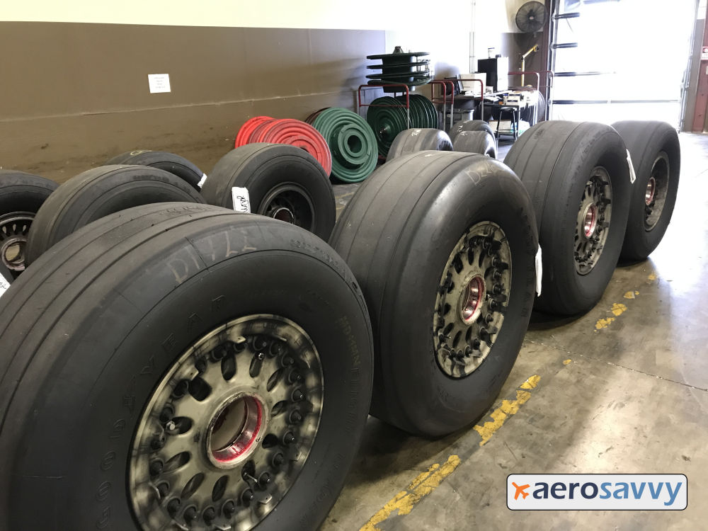 12 old, dirty wheels with worn tires stand near an overhead freight door.