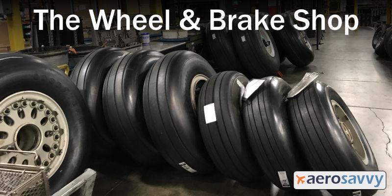 Inside the Wheel & Brake shop, 6 large, new wheels lean against each other, ready for shipment.