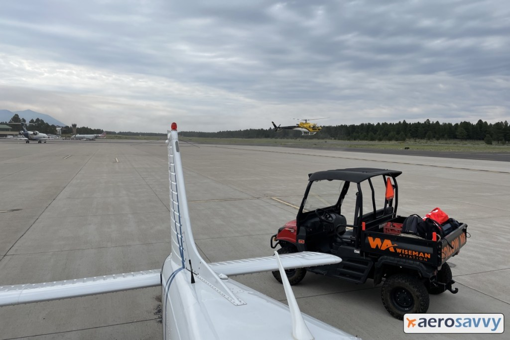 standing on our left wing looking past our tail. A yellow turbine powered helicopter lifts off.