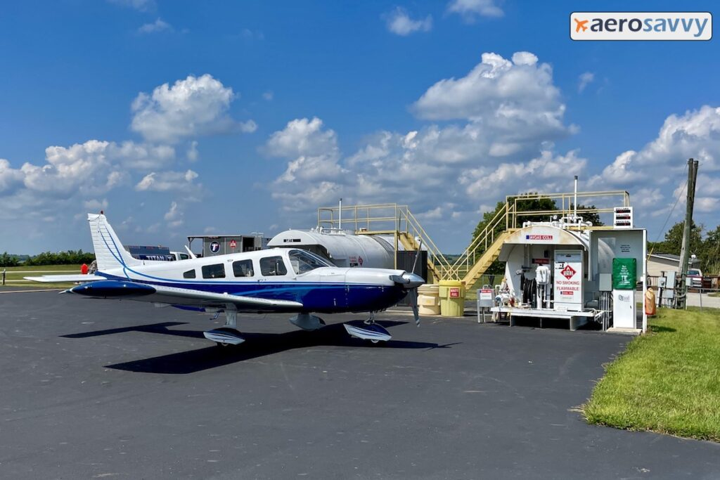 our aircraft parked next to the self-serve fuel pumps. Large, above ground fuel tanks behind the pumps.