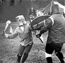 "Count Jehan fighting in a Freon can helm, soft basketball elbow and knee pads, and hockey gloves. He is using a mace nicknamed ""Feather"" which was made by Duke Andrew of Seldom Rest from a hickory axe handle and a roll of toilet paper plus lots of tape. It weighed between 4.5 and 5 pounds."