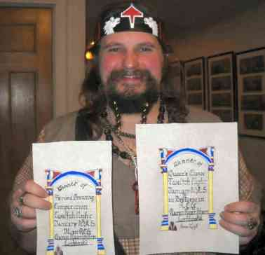 Baron Rauthbjorn with his prize scrolls, both calligraphed by Lady Lara Sukhadrev. Photo by Mistress Hilderun.