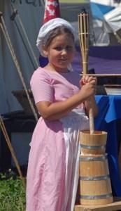 Elizabeth, daughter of Duchess Ilish, teaches butter churning.
