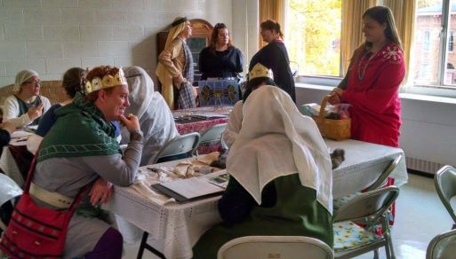Their Majesties enjoy an opportunity to learn from the artisans of Aethelmearc. Photo by Master Fridrikr Tomasson.