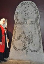 Lady Maedbh standing at runestone