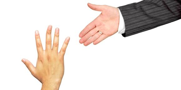 eine ausgestreckte Hand als bietet sich einer anderen an - als Symbolbild: Wie verhält sich der Ausbilder beim Modell der vollständigen Handlung?