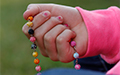 A hand grasping a colorful rosary