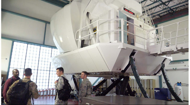 USAFA Cadets stand outside a pilot training simulator at Travis AFB.