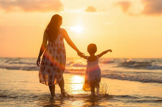 夕日の沈むビーチで散歩する親子