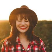 Woman outdoors smiling with sun setting in the background