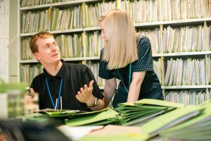 A man in a black polo shirt talking to a woman with lots of files behind them
