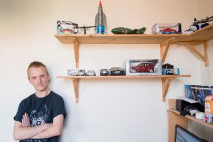 Man in T shirt standing next to a shelf of toy cars