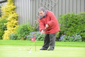 A man in an anorak playing golf
