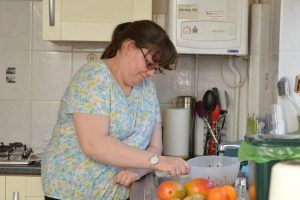 Woman with learning disability washing fruit