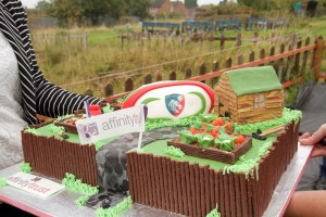 A sqaure cake with green icing and a rugby ball on top