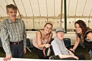 Two men with learning disabilities and two women in a marquee, smiling at the camera