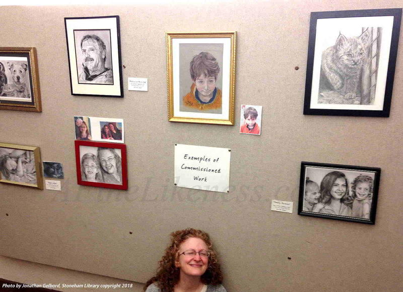 Image is of Lori Del Genis sitting below a display of her art at the Stoneham Library Show, December, 2018