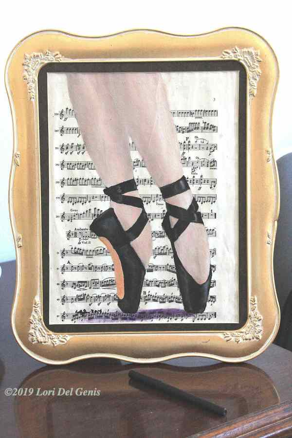 'Balance' - A ballerina's feet in black toe shoes on a background of vintage sheet music; oil painting wall or desk art by Lori Del Genis (2019).