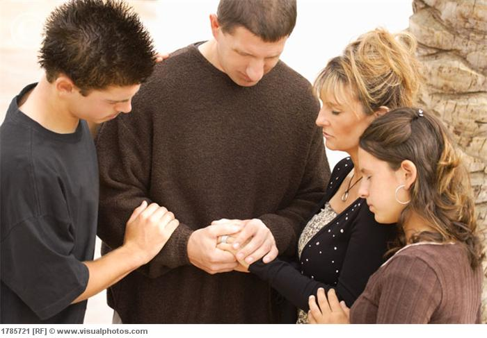 A group of young people praying together