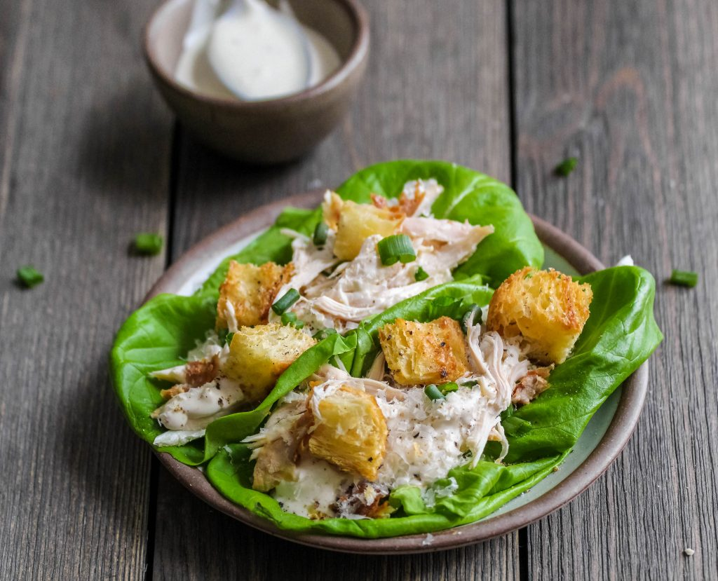soft butter lettuce wrapped around shredded rotisserie chicken, creamy greek yogurt caesar dressing, crunchy croissant croutons, and pillowy parmesan cheese. a super easy and healthy weeknight dinner idea. chicken caesar lettuce wraps | a flavor journal food blog